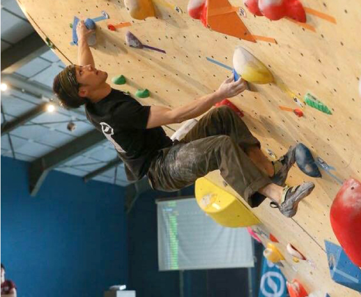 クライミングの大会にて絶対に登りきると真剣な表情の私