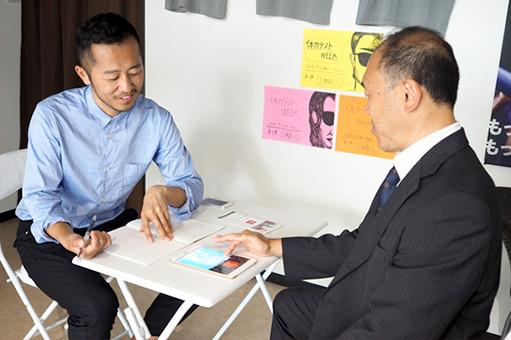 マーケティングデザインの税所とランディングページの打ち合わせをしている早川氏